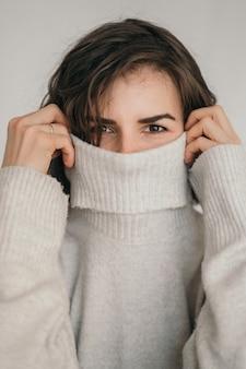 Cornice verticale di una bella bruna una foto accogliente di una ragazza con un maglione grigio la ragazza si copre il viso con una giacca ravvicinata degli occhi di una ragazza