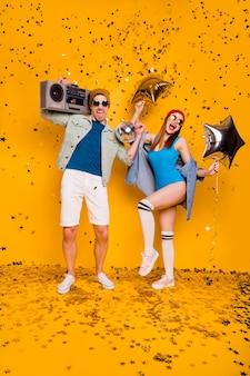 Vista verticale a figura intera delle dimensioni del corpo di una bella coppia attraente allegra eccitata felice che balla divertendosi in discoteca intrattenimento per il tempo libero isolato brillante vivido brillare vibrante sfondo di colore giallo