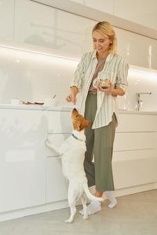 Ritratto verticale integrale di bella donna che dà delizia al cane mentre cucina una sana colazione in cucina interna