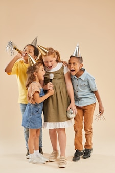 Verticale integrale ritratto di gruppo eterogeneo di bambini che indossano cappelli da festa urlando al microfono mentre posa sul beige