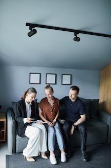 Ritratto verticale a figura intera di un agente immobiliare femminile che firma un contratto con una giovane coppia che acquista una nuova casa, copia spazio