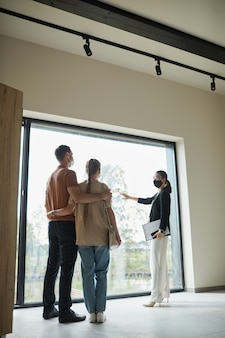 Ritratto verticale a figura intera di un agente immobiliare femminile che indossa una maschera mentre fa un tour dell'appartamento a una giovane coppia