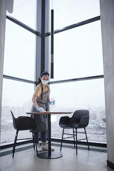 Ritratto verticale a figura intera della lavoratrice che indossa la maschera mentre pulisce i tavoli all'interno di un caffè di lusso, concetto di sicurezza covid, spazio copia