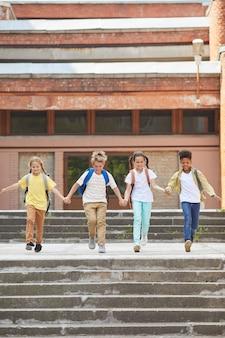 Verticale a figura intera ritratto di multietnico gruppo di bambini che lasciano la scuola con zaini e mano nella mano mentre corre verso la telecamera all'aperto, copia spazio