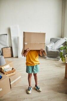 Ritratto a figura intera verticale di un adolescente con una scatola sulla testa che gioca con le cose mentre la famiglia si muove...