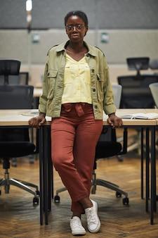 Ritratto integrale verticale di giovane donna afro-americana mentre levandosi in piedi che si appoggia sulla scrivania in ufficio moderno