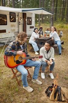 Ritratto a figura intera verticale di una giovane coppia che suona la chitarra mentre si accampa con gli amici nella foresta