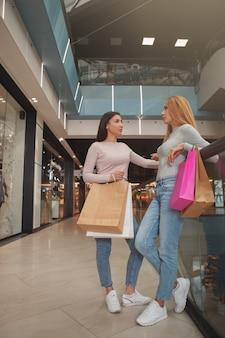 Colpo integrale verticale di due amici femminili che trasportano i sacchetti della spesa