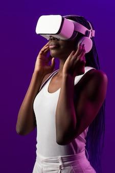 Ritratto futuristico verticale di giovane donna afro-americana che indossa l'auricolare vr su sfondo viola