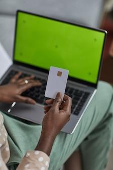 Primo piano verticale ad alto angolo di una giovane donna afro-americana che utilizza un laptop con schermo verde e tiene in mano una carta di credito, copia spazio