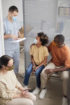 Ritratto verticale ad alto angolo di famiglia afro-americana che indossa maschere e guarda il medico mentre aspetta in fila presso la clinica medica