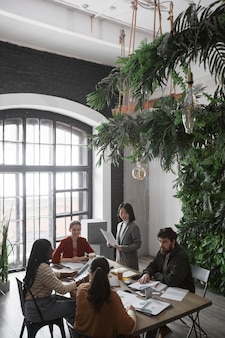 Ritratto verticale ad alto angolo di diversi gruppi di uomini d'affari che si incontrano a tavola in un ufficio moderno decorato da piante, spazio copia