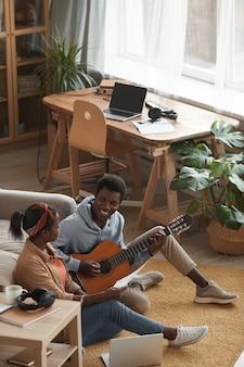 Verticale ad alto angolo ritratto di due giovani musicisti afro-americani a suonare la chitarra e scrivere musica insieme mentre è seduto sul pavimento in studio di registrazione, spazio di copia