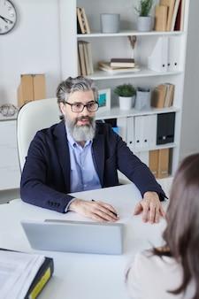 Inquadratura verticale dall'alto di un uomo maturo con la barba sul viso che intervista un nuovo dipendente in un ufficio moderno
