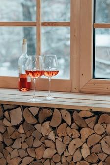 Un'immagine verticale di una bottiglia di vino e bicchieri sul davanzale di una finestra