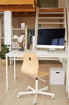 Immagine verticale dell'interiore contemporaneo dell'appartamento a due livelli con il posto di lavoro dell'ufficio domestico nella priorità alta