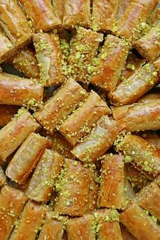 Immagine verticale di deliziosi pasticcini al baklava conditi con pistacchi tritati