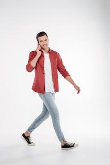 Immagine verticale dell'uomo felice che cammina e che parla sul telefono