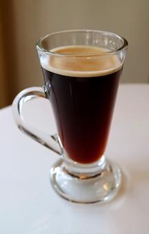 Immagine verticale di caffè nero caldo in vetro trasparente isolato sul tavolo bianco
