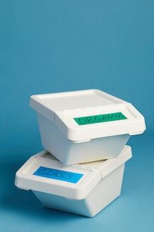 L'immagine verticale di bidoni della spazzatura etichettati per vetro e rifiuti organici, concetto di smistamento e riciclaggio