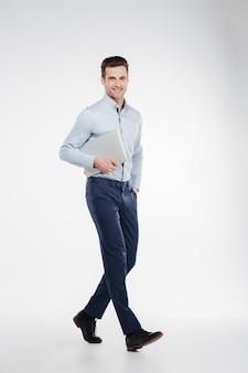 Immagine verticale dell'uomo sorridente di affari che cammina con il computer portatile