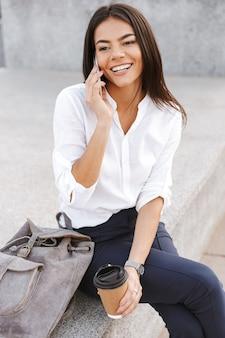 L'immagine verticale della donna sorridente di affari che si siede all'aperto