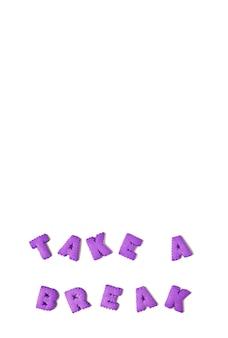 L'immagine verticale del testo prendi una pausa fatta con i biscotti di alfabeto viola su fondo bianco