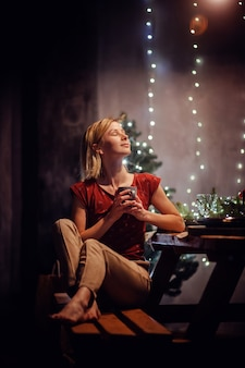 Foto chiave bassa verticale della ragazza dei capelli biondi in maglietta rossa e pantaloni beige che tiene la tazza che si siede da solo sulla panca di legno vicino al tavolo servito davanti al muro grigio con le luci della ghirlanda
