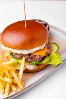 Menu verticale con hamburger di manzo con salsa e patate fritte sul tavolo bianco