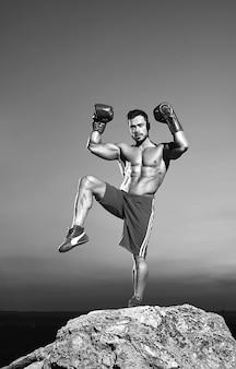 Colpo verticale monocromatico di un combattente maschio professionista che indossa guanti da boxe che si esercita all'aperto sulla cima di una roccia muscoli forza potenza agilità atleta sportivo pugile arti marziali combattimento competere.