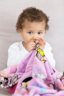 Foto verticale del bambino che tiene seduta coperta.