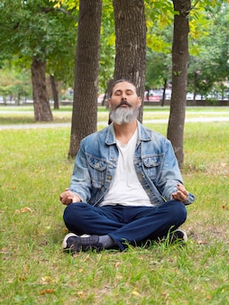 Foto verticale di un uomo di mezza età barbuto che si prende una pausa dal trambusto della città che ...