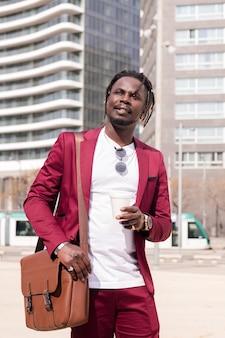 Foto verticale di un elegante uomo d'affari nero che cammina attraverso il centro finanziario della città con un caffè e una valigetta, copia spazio per il testo