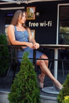 Foto verticale di una ragazza in un caffè. una ragazza in una cima blu si siede lateralmente. zona wi-fi.