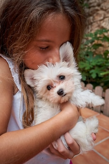 Foto verticale di una ragazza che bacia un cagnolino bianco tenuto tra le braccia