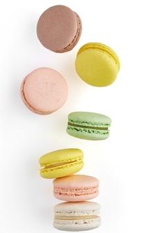 Foto verticale di amaretto. macaron torta colorata con toni pastello cadono al maccherone pila sulla superficie bianca. vista dall'alto di biscotti alle mandorle.