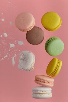 Foto verticale di amaretto. macaron torta colorata con toni pastello e amaretto bianco incrinato con briciole in levitazione caotica cadono alla pila sul muro di rose. vista dall'alto di biscotti alle mandorle.