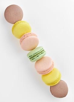 Foto verticale di amaretto. macaron di torte colorate con toni pastello disposti in una striscia dall'angolo della cornice a un altro angolo sulla superficie bianca. vista dall'alto di biscotti alle mandorle.