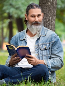 Foto verticale di un uomo di mezza età con un libro nel parco si siede sull'erba nel parco e guarda...