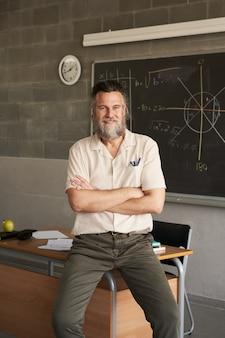 Foto verticale di un insegnante maschio barbuto di mezza età che guarda la telecamera con le braccia incrociate in classe