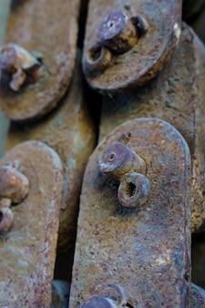 Foto verticale di vecchi pezzi di ferro arrugginito collegati tra loro vintage e antico concetto