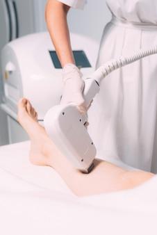 Foto verticale del processo di depilazione laser su una gamba, dal ginocchio in giù.