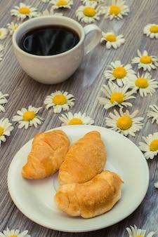 Foto verticale di una colazione romantica e gustosa. croissant e tazza di caffè sulla tavola di legno con le camomille Foto Premium