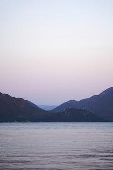 Foto verticale del mare e delle colline nel crepuscolo. in viaggio verso la natura