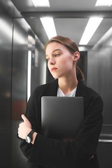 Foto verticale di giovane imprenditrice seria che tiene il suo computer portatile nell'ascensore.