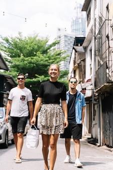 Foto verticale di tre giovani di diversa etnia e genere che sorridono e camminano per una strada con automobili, alberi e luci appese mentre la donna tiene in mano una borsa