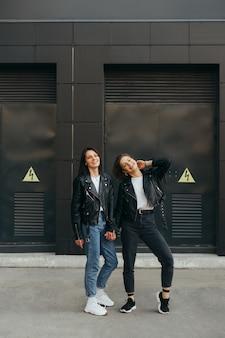 Foto verticale di due amiche felici che hanno divertimento sulla parete nera