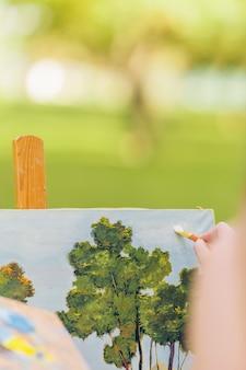 Foto verticale con messa a fuoco selettiva sulla pittura a mano di una donna con un pennello su una tela
