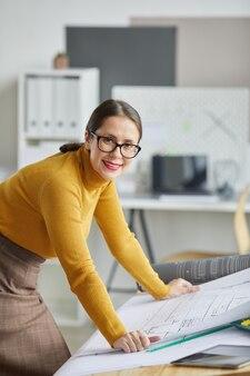 Ritratto verticale dell'architetto femmina adulta che sorride alla macchina fotografica mentre si appoggia sulla scrivania in ufficio e lavora sui progetti