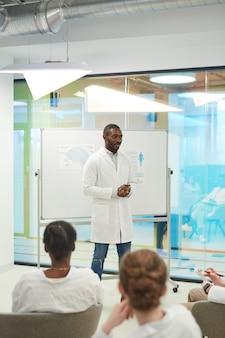 Ritratto verticale di un uomo afro-americano in piedi davanti alla lavagna mentre tiene un seminario di medicina al college, copia spazio